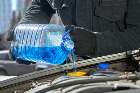 Man filling a windshield washer tank of a car by antifreeze in winter outdoors