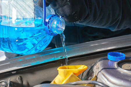 Filling a windshield washer tank of a car with a wiper fluid outdoors Stock Photo