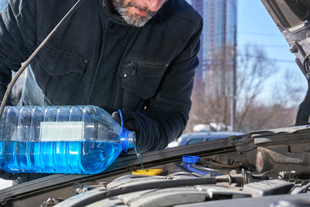 Man filling a windshield washer tank of a car by antifreeze on winter Moscow street