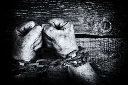 Black and white image of the powerful dirty male hands clenched into fists chained with rusty chain on wooden background with copy space Stock Photo
