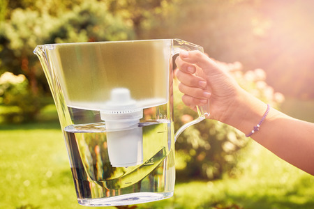 Girl's hand holds a water filter jug illuminated by sun rays in a sunny summer garden in a warm day in countryside Banque d'images