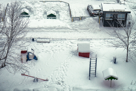 Usual Moscow yard with children playground and ice-cream trading kiosk in snowy winter. View from above from a window of a house. Stock Photo