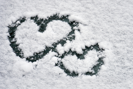 Two hearts symbols drawn in the white snow on a car windshield in winter. Valentines day concept. Stock Photo
