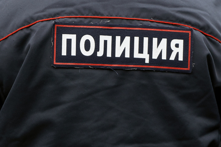 Russian policemans back wearing an uniform close up with an emblem Police