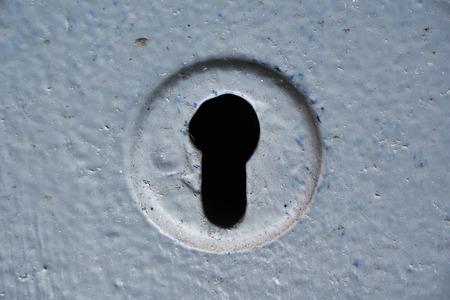 Dark keyhole in a grey metal painted door