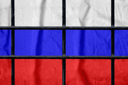 Russian flag behind black metal bars of a prison grate without shadows. Symbol of oppression of freedom in Russia