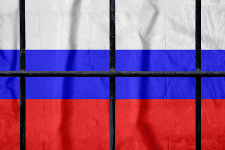Russian flag behind black metal prison bars Stock Photo
