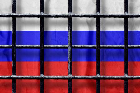 Bandiera russa dietro le sbarre di metallo nero di una grata di una prigione con ombre. Simbolo dell'oppressione della libertà in Russia Archivio Fotografico