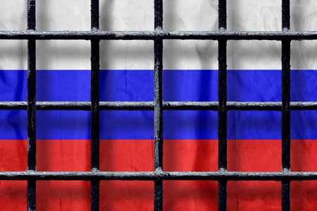 Russian flag behind black metal bars of a prison grate with shadows. Symbol of oppression of freedom in Russia