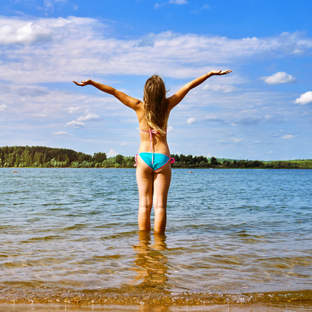 Teenager girl with raised hands stands in the water of a beautiful lake and enjoys warm weather at summer vacations