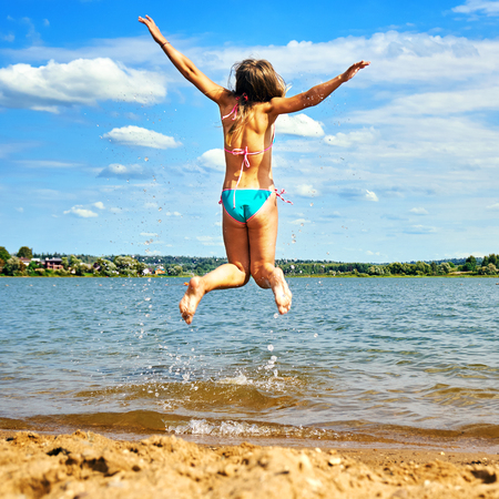 Teenager girl wearing bikini with spreading hands jumps high above the water of a beautiful lake enjoying warm weather at summer vacations. Happy summer vacations.