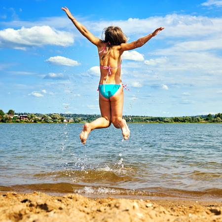 Tienermeisje in bikini met spreidende handen springt hoog boven het water van een prachtig meer en geniet van warm weer tijdens zomervakanties. Fijne zomervakanties. Stockfoto