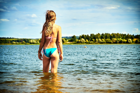 Teenager girl wearing bikini stands in the water of a beautiful lake and enjoys warm weather at summer vacations