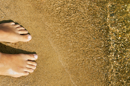 Teen girl's feet standing on the sand of a lake beach near the water on summer vacations. Concept of a rest on the beach in summer heat