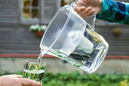 Girls hand pours clear filtered water from a water filtration jug into a glass which female hand holds in front of a country house 스톡 콘텐츠