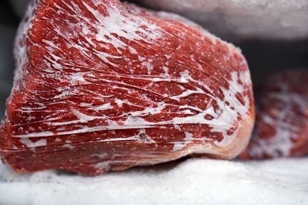 Large pieces of red meat in a freezer with a big quantity of frozen ice and snow Фото со стока