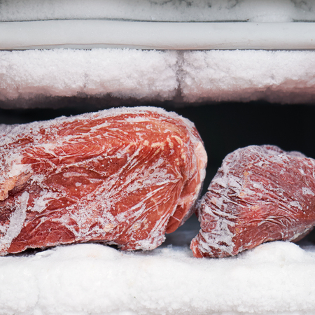 Large pieces of red meat in a freezer with a big quantity of frozen ice and snow Archivio Fotografico