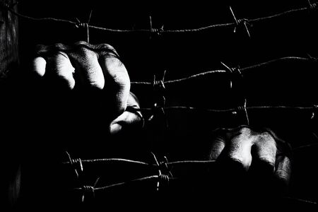 Dirty male hands hold stretched rusty barbed wire in the dark of the night lit by the hard light of the prison lamps. Unfreedom concept. Black and white photo.