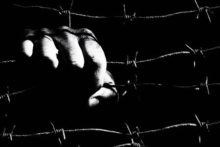 Dirty male hand holds stretched rusty barbed wire in the dark of the night lit by the hard light of the prison lamps. Unfreedom concept. Black and white photo.