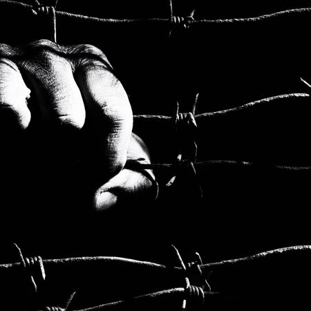 Dirty male hand holds stretched rusty barbed wire in the dark of the night lit by the hard light of the prison lamps. Unfreedom concept. Black and white square photo