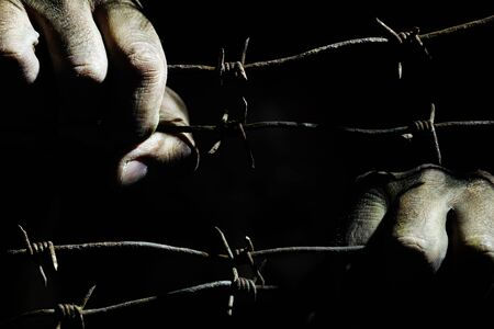 Dirty male hands hold stretched rusty barbed wire in the dark of the night lit by the hard light of the prison lamps. Unfreedom concept.