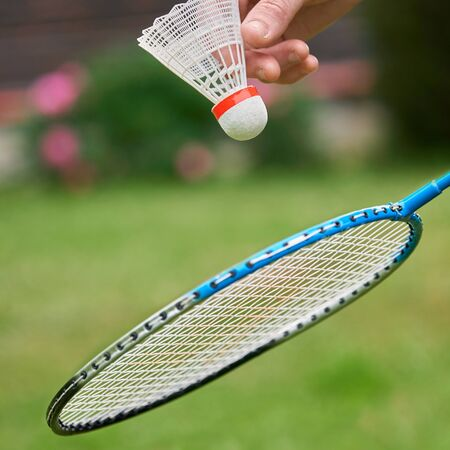 Middle-aged womans hand holds a white badminton shuttlecock and a racket outdoors with green grass and pink flowers on the background . Active sports games in the summer garden outdoors