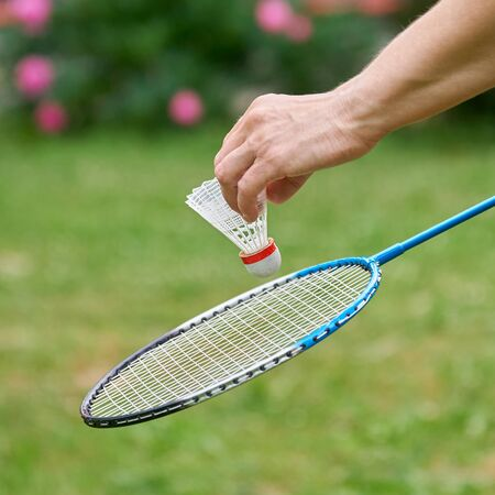Middle-aged woman's hand holds a white badminton shuttlecock and a racket outdoors with green grass and pink flowers on the background . Active sports games in the summer garden outdoors Stock Photo