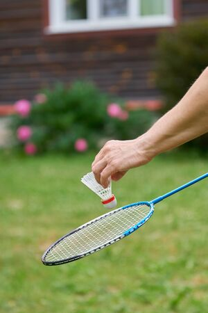 Middle-aged womans hand holds a white badminton shuttlecock and a racket outdoors in front of a country house . Active sports games in the summer garden outdoors
