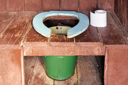 Toilet seat of a country wooden outdoor toilet with a metal bucket as a waste tank and a roll of a paper close up Reklamní fotografie