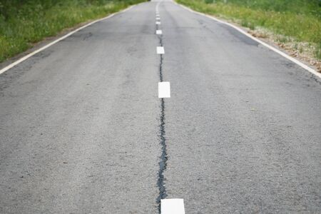 Fragment of a grey shabby car asphalt road with white dividing lines and green grass on the roadsides Banco de Imagens