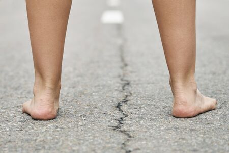 Rear view of bare feet of a young girl standing on the asphalt road close up.