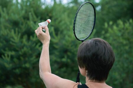 Brunette woman plays badminton outdoors in summer evening with green trees foliage on the background . Active sports games in the summer garden outdoors Banco de Imagens