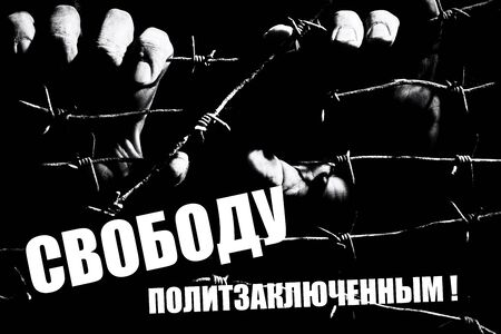 Male hands hold stretched barbed wire in the dark lit by the hard light of the prison lamps with a russian writing. Translation: Freedom for political prisoners . Unfreedom concept. Black and white.