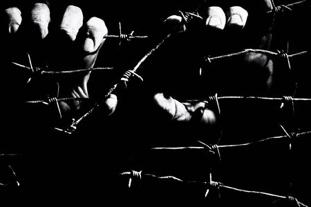 Male hands hold stretched rusty barbed wire in the dark of the night lit by the hard light of the prison lamps. Unfreedom concept. Black and white photo.