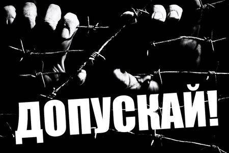Hands hold barbed wire in the dark lit by the light of lamps with a russian writing. Translation: Allow. This is a the slogan of the protesters against the non-admission to the elections to the Moscow city Duma of independent candidates in july 2019