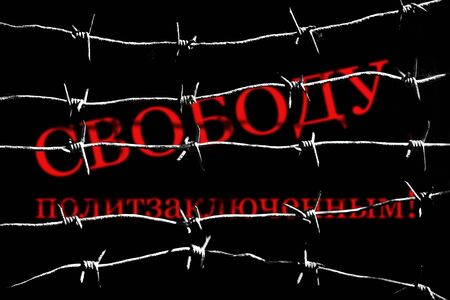 Freedom for political prisoners on russian wrote with red paint behind white silhouettes of barbed wires