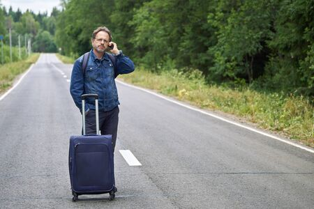 Man with a luggage standing in the middle of a asphalt road and speaks on mobile phone