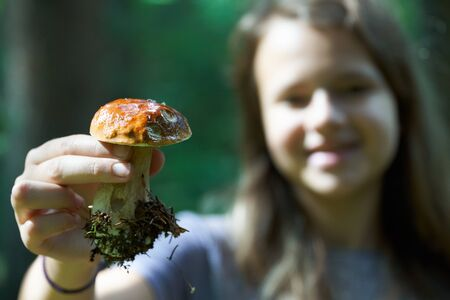 Teen Girl showing a mushroom boletus edulis in hand in the forest