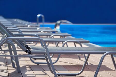 Empty sunbeds standing near a swimming pool with blue water in summer Banco de Imagens