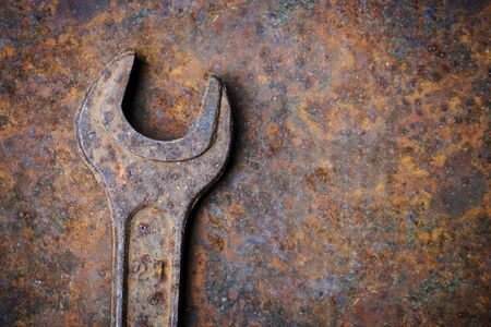 Old rusty wrench lying on the rusty textured metal background. Mechanic background Banco de Imagens