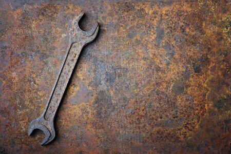 Alter rostiger Schraubenschlüssel, der auf dem rostigen strukturierten Metallhintergrund liegt. Mechaniker Hintergrund
