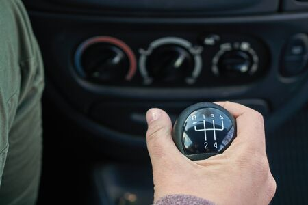 Young girl is switching gears in the car with a manual gearbox using gearshift