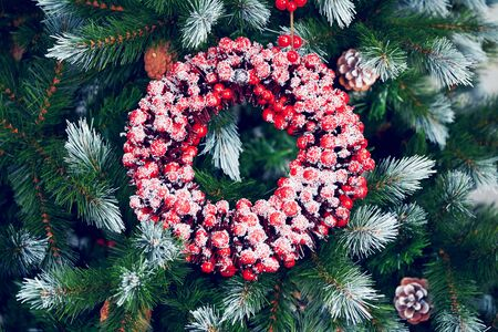 New Years background with a Christmas wreath made from a red berry on the decorated green Christmas tree branches