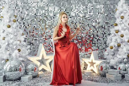 Chica guapa joven en vestido rojo posando con adornos de año nuevo en el fondo