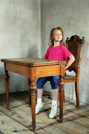 Little girl sitting at the ancient wooden table in the cell of monastery Stockfoto