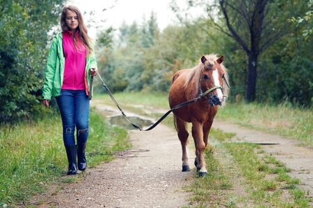 Teenage girl walking with a pony colt on a leash along a country dirt road