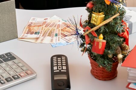 Bonus money lying on a working table in the office in New Year or Christmas eve. There are calculator, phone, decorated Christmas tree and russian money on the desk