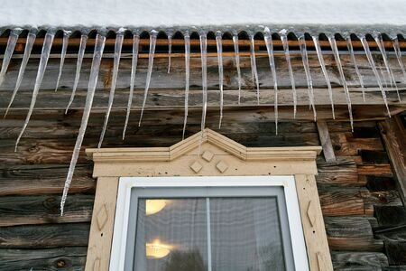 Large dangerous icicles hanging on the roof of a wooden country house in winter or spring in Russia.