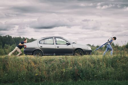 Man and a woman pushing their broken car down the country road. Middle-aged couple trying to bring the car to the car service station in summer cloudy day during journey