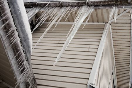 Long heavy icicles hanging on the roof of a house in cold winter